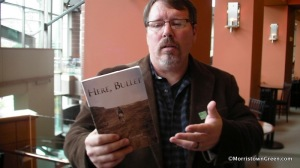 "Turner holding his book of poems ""Here, Bullet"". Courtesy of morristowngreen.com"